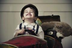 Jeune garçon heureux dans la voiture en bois Photo stock
