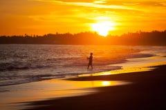 Jeune garçon heureux de pêcheur au coucher du soleil sur la plage Images stock