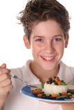 Jeune garçon heureux mangeant le riz, les haricots et le veggi sains photos stock