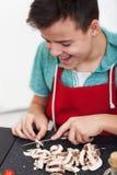 Jeune garçon heureux préparant un plat dans la cuisine - champignons de tranche sur la planche à découper photos libres de droits