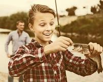 Jeune garçon heureux tenant dessus le poisson d'eau douce de crochet Photographie stock libre de droits