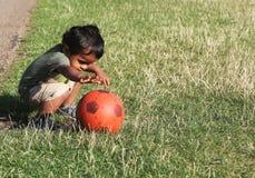 Jeune garçon indien jouant dans l'herbe avec la boule Photographie stock libre de droits