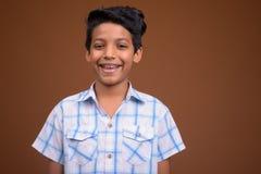Jeune garçon indien utilisant la chemise à carreaux contre le backgroun brun image stock