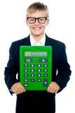 Jeune garçon intelligent retenant la grande calculatrice verte images libres de droits
