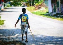 Jeune garçon jamaïcain de la préadolescence noir marchant sur seule la rue images stock