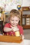 Jeune garçon jouant à Montessori/à école maternelle Photos stock