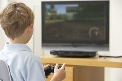 Jeune garçon jouant avec la console de jeu Photo stock