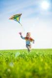 Jeune garçon jouant avec son cerf-volant dans un domaine vert Photographie stock