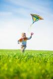 Jeune garçon jouant avec son cerf-volant dans un domaine vert Photos libres de droits