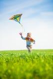 Jeune garçon jouant avec son cerf-volant dans un domaine vert Image stock