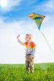 Jeune garçon jouant avec son cerf-volant dans un domaine vert Photo libre de droits