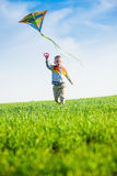 Jeune garçon jouant avec son cerf-volant dans un domaine vert Photo stock