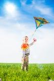 Jeune garçon jouant avec son cerf-volant dans un domaine vert Photos stock