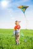 Jeune garçon jouant avec son cerf-volant dans un domaine vert Photographie stock libre de droits