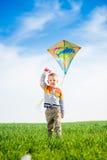 Jeune garçon jouant avec son cerf-volant dans un domaine vert Images libres de droits