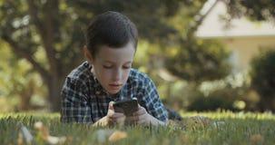 Jeune garçon jouant avec un smartphone clips vidéos