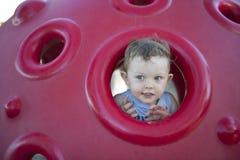 Jeune garçon jouant dans la cour de jeu images libres de droits