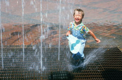 Jeune garçon jouant dans la fontaine d'eau Images stock