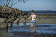 Jeune garçon jouant en eau peu profonde photos libres de droits