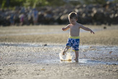 Jeune garçon jouant en eau peu profonde image libre de droits