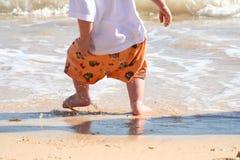 Jeune garçon jouant en vague déferlante Photo stock