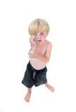 Jeune garçon jouant la guitare de carton avec le fond blanc Images stock