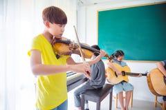 Jeune garçon jouant le violon dans la salle de classe Image stock