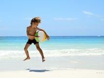Jeune garçon jouant sur la plage tropicale Image libre de droits