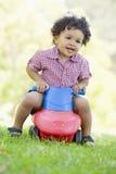 Jeune garçon jouant sur le jouet avec des roues à l'extérieur Photographie stock libre de droits
