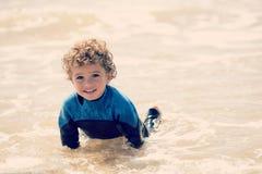 Jeune garçon jouant sur le rivage Images stock