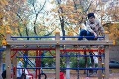 jeune garçon jouant sur le terrain de jeu en parc en automne images libres de droits
