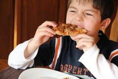 Jeune garçon mangeant de la pizza Photo libre de droits