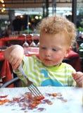 Jeune garçon mangeant de la pizza image stock