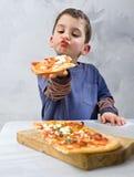 Jeune garçon mangeant de la pizza image libre de droits