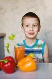 Jeune garçon mangeant la pomme et les légumes Images libres de droits