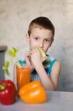 Jeune garçon mangeant la pomme et les légumes Photos libres de droits