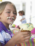 Jeune garçon mangeant le petit gâteau à la fête d'anniversaire Photos libres de droits