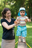 Jeune garçon marchant avec sa mère sur le banc Image stock