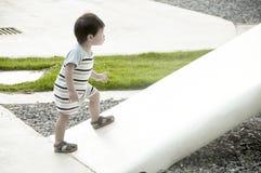 Jeune garçon montant sur une pente Images stock