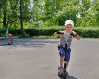 Jeune garçon montant un scooter en parc Photographie stock