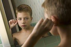 Jeune garçon nettoyant ses oreilles photographie stock libre de droits