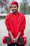 Jeune garçon noir avec le mini scooter segway électrique de conseil de vol plané Images stock