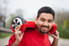 Jeune garçon noir avec le mini scooter segway électrique de conseil de vol plané Photos stock