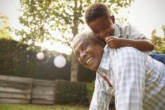 Jeune garçon noir s'élevant sur son dos du ½ s de ¿ de grandfatherï dans le jardin Images libres de droits
