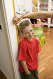 Jeune garçon obtenant la mesure de taille en porte Image stock