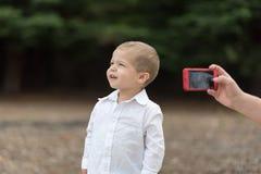 Jeune garçon obtenant la photo prise Image libre de droits