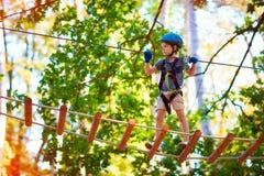 Jeune garçon passant la haute d'itinéraire de câble parmi des arbres, sport extrême en parc d'aventure Photos libres de droits