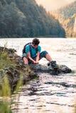 Jeune garçon prenant l'eau pure d'une rivière et la tenant dans les mains image stock