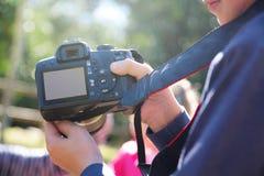 Jeune garçon prenant tenant un appareil-photo prenant quelques photos avec ses amis dans la nature Photos stock