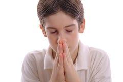 Jeune garçon priant au centre blanc photographie stock